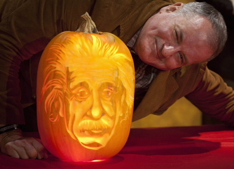 Pumpkin carver Hugh McMahon poses with the Albert Einstein pumpkin that he carved at Madame Tussauds in New York, October 22, 2013. (Carlo Allegri/Reuters photo)