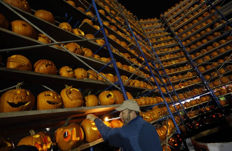 A volunteer lights a carved pumpkin, one of the thousands of carved pumpkins on display, at the Great Highwood Pumpkin Festival in Highwood, Illinois, October 18, 2013. Organizers are trying to set the Guinness Book of World Records for the most lit jack-o'-lanterns on display. (Jim Young/Reuters photo)