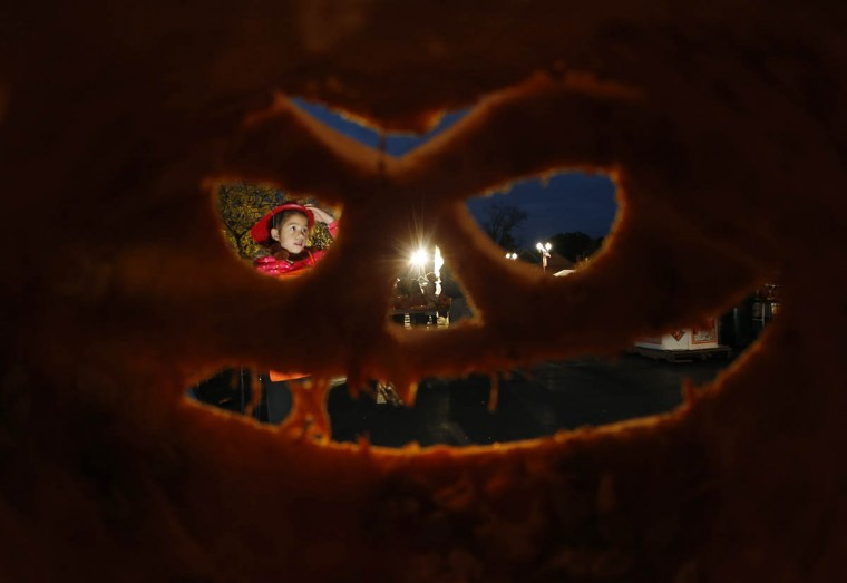 A girl is seen through one of the thousands of carved pumpkins on display at the Great Highwood Pumpkin Festival in Highwood, Illinois, October 18, 2013. Organizers are trying to set the Guinness Book of World Records for the most lit jack-o'-lanterns on display. (Jim Young/Reuters photo)