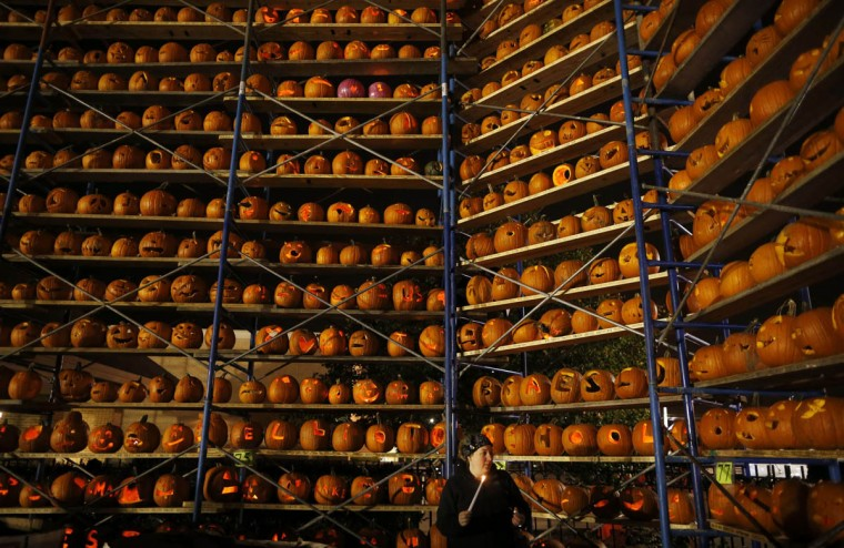 A woman holds a candle next to a rack of carved pumpkins on display at the Great Highwood Pumpkin Festival in Highwood, Illinois, October 18, 2013. Organizers are trying to set the Guinness Book of World Records for the most lit jack-o'-lanterns on display. (Jim Young/Reuters photo)