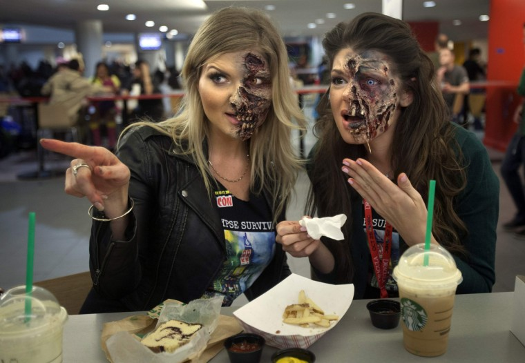Makeup artists Kamila Wysocka and Alexis Jackson from Florida point at another costumed person as they eat dinner in their zombie makeup at ComicCon in New York. (Carlo Allegri/Reuters)
