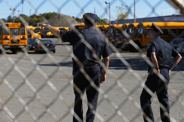 Boston police officers stand in a school bus yard where drivers walked off the job in the morning in Boston, October 8, 2013. Boston Mayor Thomas Menino vowed to punish school bus drivers who walked off the job on Tuesday in a labor action the city contended was illegal, and which even the drivers' union organization condemned. Some 33,000 public and private school students were left to find alternative routes to school on Tuesday after a union representing some 700 drivers and also represented by the United Steelworkers of America Local 8751 did not show up for work. (Brian Snyder/Reuters)