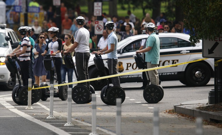 Tourists on a Segway tour watch law enforcement officers secure an entrance to the White House and Treasury Department where a car chase began, ending in gunfire outside the U.S. Capitol in Washington, October 3, 2013. The U.S. Capitol was locked down briefly on Thursday after gunshots were fired outside the building following the car chase across central Washington and a number of people including a law enforcement officer were hurt, officials said. There was no apparent connection to terrorism in the car chase, a U.S. official said. (Jonathan Ernst/Reuters)