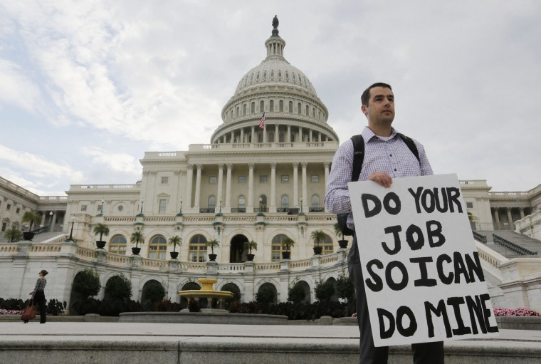 A furloughed federal employee holds a sign on the steps to the U.S. Capitol after the U.S. Government shut down last night, on Capitol Hill in Washington October 1, 2013. The U.S. government began a partial shutdown for the first time in 17 years, potentially putting up to 1 million workers on unpaid leave, closing national parks and stalling medical research projects. (Larry Downing/Reuters photo)