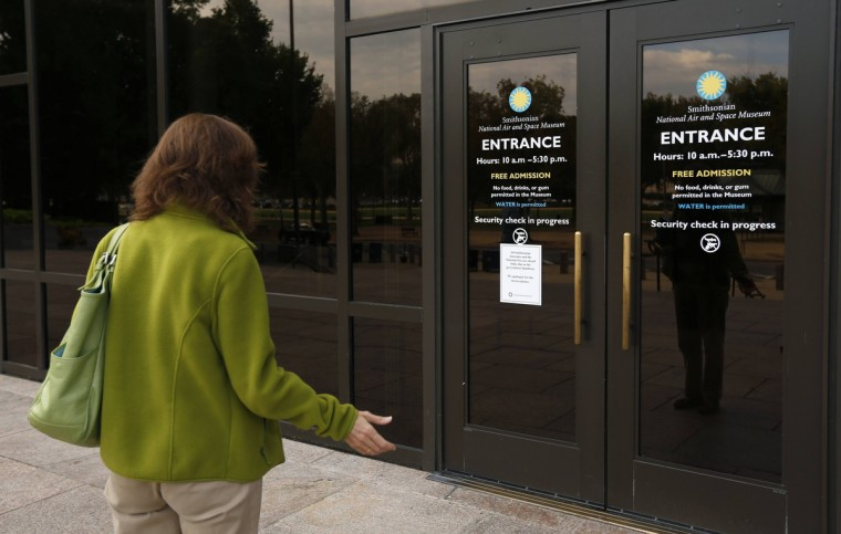 Fernanda Wagstaff holds her hand out in disbelief as she reads a sign at the Air and Space Museum informing visitors that all Smithsonian museums are closed, in Washington October 1, 2013. (Kevin Lamarque/Reuters photo)