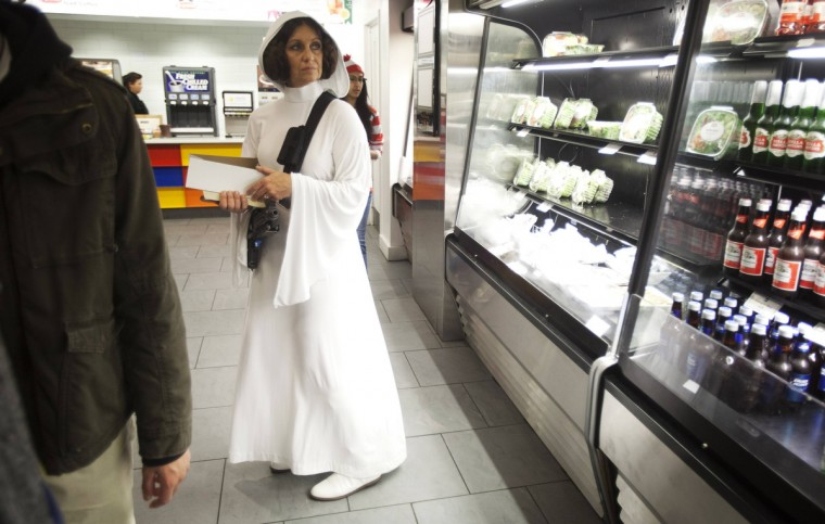 A woman dressed as Princess Leia from Star Wars waits in line to buy food at ComicCon in New York. (Carlo Allegri/Reuters)
