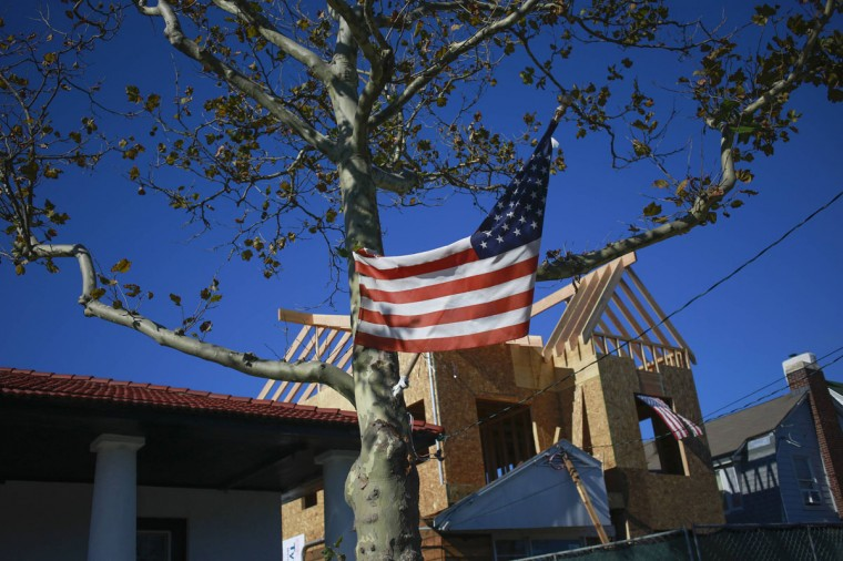 An American flag hangs from a tree as construction is done on a home damaged by hurricane Sandy in October 2012 in the Belle Harbor section of the borough of Queens in New York October 24, 2013. Progress is being seen to areas along the beachfront area while others remain damaged with just days until the one year anniversary of the storm. (Shannon Stapleton/Reuters)