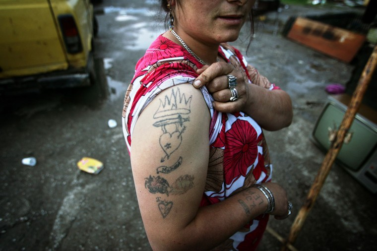 A Roma woman shows her tattoos, telling about her life full of death and sorrow, on St. George's Day or Djurdjevdan in the Roma settlement in Sarajevo's suburb of Butmir May 6, 2006. Around 100.000 members of Roma minority in Bosnia celebrate their biggest holiday St. George's Day slaughtering lambs and spending the day in good mood with relatives and neighbours. (Damir Sagolj/Reuters)