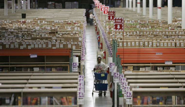 A worker collects products for shipment to customers at the Amazon.com warehouse facility in New Castle, Delaware, November 24, 2006. The November-December holiday shopping season is the most important period for U.S. Retailers. (Tim Shaffer/Reuters)