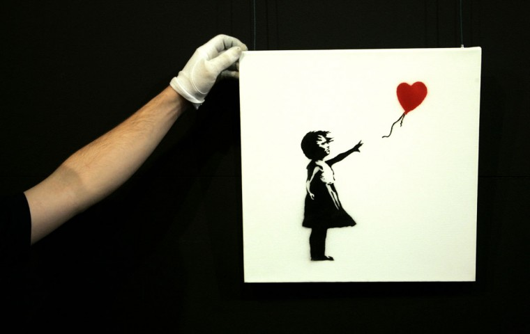 """A gallery technician adjusts Banksy's artwork """"Balloon Girl"""" (1975) at Sotheby's auction house at Olympia in London on February 2, 2007. (REUTERS / Luke MacGregor )"""
