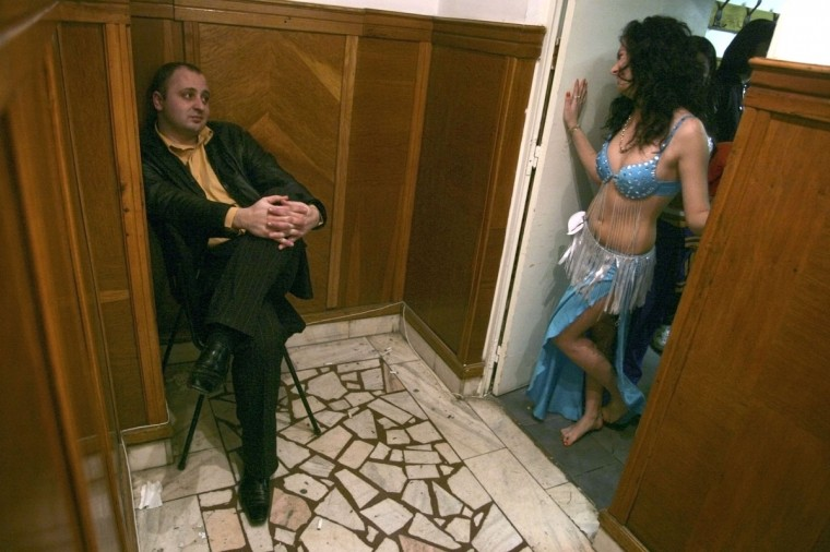 "A man guards the entrance of the room where Romanian gypsy girls are preparing for the ""Miss Piranda"" (gypsy girl) contest in Bucharest, late February 4, 2007. The jury will base their decision not just on the contestants' beauty, but also on their belly dancing skills. (Mihai Barbu/Reuters)"