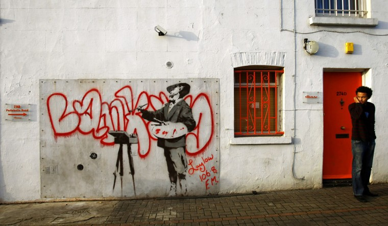A man chats on his phone beside a painting on a wall in Portobello Road, west London on January 14, 2008. (REUTERS/Dylan Martinez )