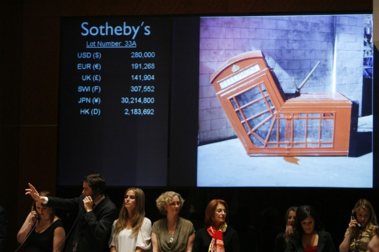 """An employee signals a phone bid for Banksy's """"Vandalised Phone Box"""" during Sotheby's """"Red"""" benefit auction to raise funds for HIV/AIDS treatment in Africa in New York on February 14, 2008. (REUTERS/Lucas Jackson)"""