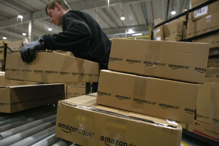 A worker carries packages for shipment at the Amazon warehouse in Leipzig, December 3, 2008. The shelves at the company's warehouse become full during the busiest time of the year before Christmas. (Fabrizio Bensch/Reuters)