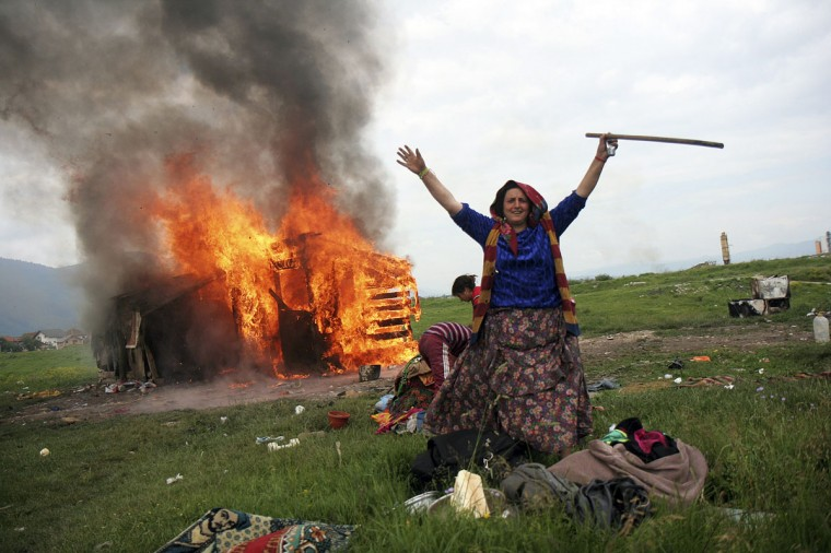 A Roma woman gestures in front of her burning home at a Roma settlement in Sarajevo's suburb of Butmir June 3, 2009. The community set their homes on fire as they were forced to move to new houses provided by the local government.