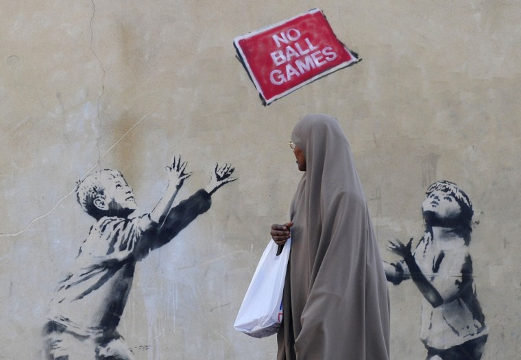 A pedestrian passes graffiti art on a wall in north London on September 24, 2009. (REUTERS/Toby Melville)