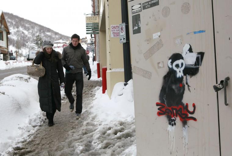 Pedestrians walk past artwork by Banksy during the Sundance Film Festival in Park City, Utah on January 22, 2010. (REUTERS/Robert Galbraith)