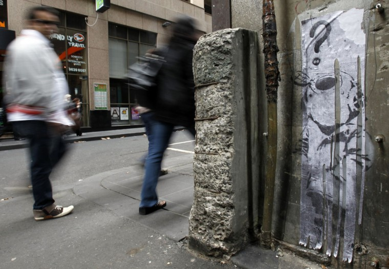 """People walk past a vinyl replacement of the street art stencil titled """"Little Diver"""" by British street artist Bansky in central Melbourne on April 28, 2010. (REUTERS/Mick Tsikas)"""