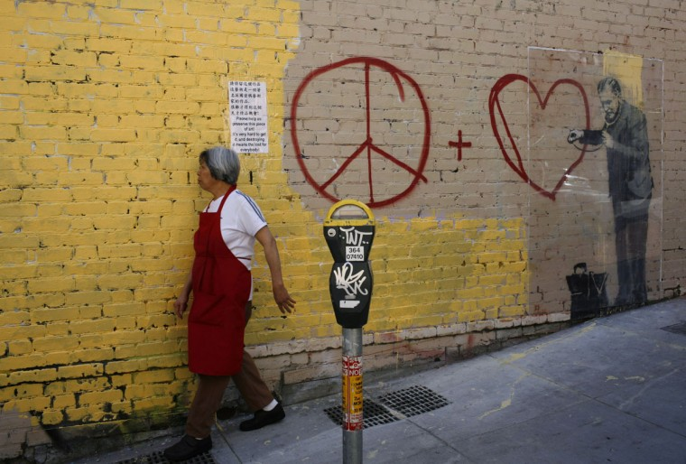 A woman walks past a painting, believed to be the work of elusive British street artist Banksy, in the Chinatown section of San Francisco on May 4, 2010. (REUTERS/Robert Galbraith )