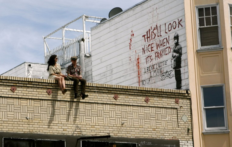 A couple sits on a rooftop featuring a painting, believed to be the work of elusive British street artist Banksy, in the Mission District of San Francisco on May 4, 2010. (REUTERS/Robert Galbraith)