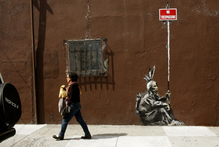 A woman walks past a drawing, believed to be the work of elusive British street artist Banksy, in the Mission District of San Francisco on May 4, 2010. (REUTERS/Robert Galbraith)