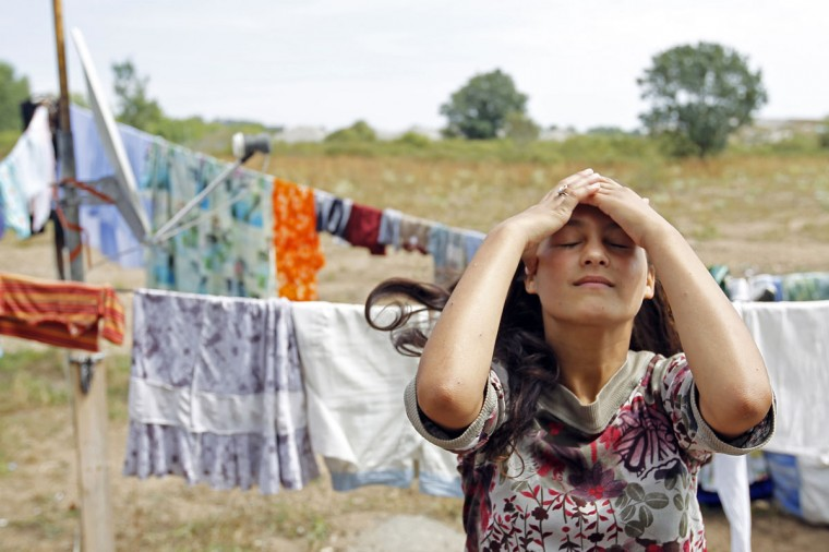 "A teenage girl fixes her hair near hanging laundry inside an illegal camp of travelling people in Indre, near Nantes, western France, on July 30, 2010. President Nicholas Sarkozy on Wednesday ordered the dismantling of 300 illegal camps of travelling people and Roma across France, as part of a ""war"" on crime and urban violence which has alarmed some rights groups. Some 10,000 Roma were expelled from France last year alone. (Stephane Mahe/Reuters)"