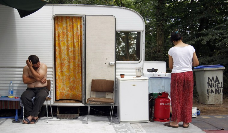 "A woman cooks outside her caravan at an illegal camp of travelling people in Le Chemin Nantais, near Nantes, western France, on July 30, 2010. President Nicholas Sarkozy on Wednesday ordered the dismantling of 300 illegal camps of travelling people and Roma across France, as part of a ""war"" on crime and urban violence which has alarmed some rights groups. Some 10,000 Roma were expelled from France last year alone. (Stephane Mahe/Reuters)"