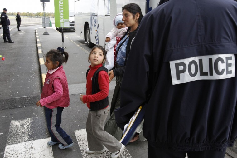 A Roma family walks past a policeman as they arrive at the Lille-Lesquin airport for their flight to Romania on a voluntary repatriation scheme September 16, 2010.The European Union threatened France with legal action over its handling of the expulsion of Roma migrants on Tuesday, with the EU's justice commissioner calling France's behaviour unacceptable and a disgrace. (Pascal Rossignol/Reuters)