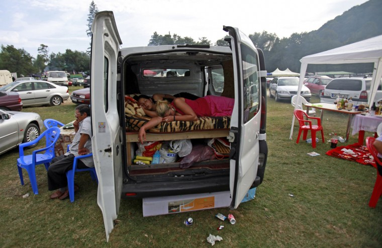 Two Roma women sleep inside a van during the gathering of the ethnic Roma minority in Costesti, 210 km (128 miles) west of Bucharest, September 8, 2011 Following their tradition, thousands of Roma from all over Romania, which has Europe's largest Roma community, gather every year to celebrate the birthday of St. Mary, to make wedding arrangements for their sons and daughters and to show off their wealth. (Radu Sigheti/Reuters)