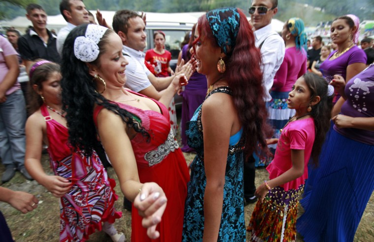 Two Roma girls dance during a gathering of the ethnic Roma minority in Costesti, 210 km (128 miles) west of Bucharest, September 8, 2011. Following their tradition, thousands of Roma from all over Romania, which has Europe's largest Roma community, gather every year to celebrate the birthday of St. Mary, to make wedding arrangements for their sons and daughters and to show off their wealth. (Radu Sigheti/Reuters)