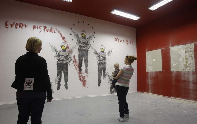 """Visitors look at the work """"Every Picture Tells A Lie"""" by street artist Banksy at the Kuenstlerhaus Bethanien in Berlin on September 13, 2011. (REUTERS/Tobias Schwarz)"""