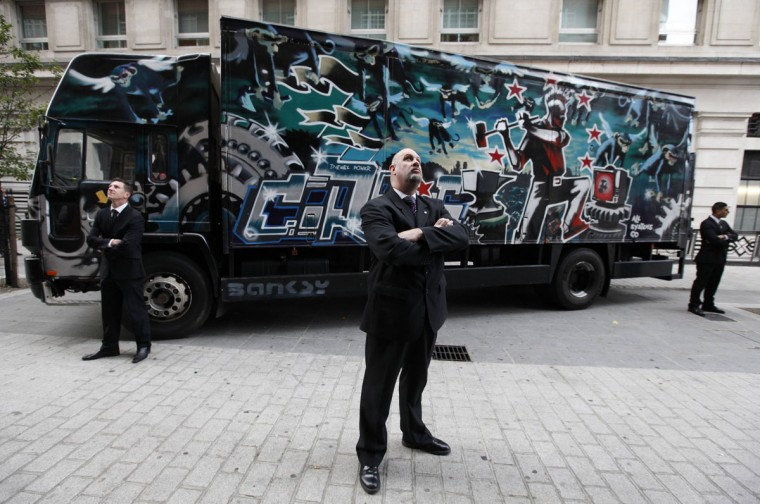 Security guards pose for a photograph next to a truck covered with artwork by street artist Banksy in London on October 6, 2011. (REUTERS/Suzanne Plunkett )