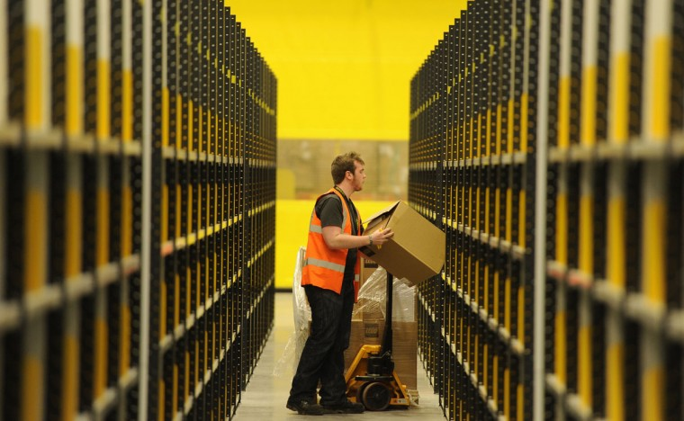 A worker lifts a box at Amazon's new fulfilment centre after it was opened by Scotland's First Minister Alex Salmond in Dunfermline, Scotland, November 15, 2011.The warehouse covers more than one million square feet (93,000 square metres), about the size of 14 soccer pitches, and is Amazon?s biggest in the United Kingdom. It will create 750 permanent jobs, along with a further 1,500 temporary jobs during peak periods. (Russell Cheyne/Reuters)