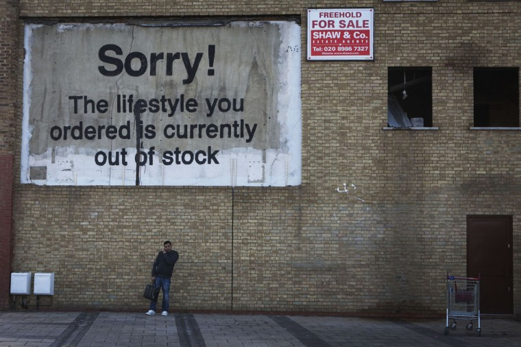 A new work by British artist Banksy, in the form of a billboard, adorns a wall near the Canary Wharf financial district in London on December 22, 2011. (REUTERS/Finbarr O'Reilly)