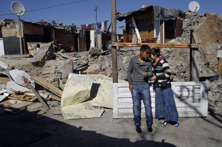 "A man and his young wife share a moment next to the debris of their neighbours' demolished shack in the shanty town settlement of ""El Gallinero"" on the outskirts of Madrid March 5, 2012. A handful of shacks were torn down under the orders of Madrid's town planning board on Monday morning. Several hundred Romanian gypsies live in precarious conditions, without running water or sewage services, in ""El Gallinero"", just 15 km (9 miles) away from Madrid's centre. (Susana Vera/Reuters)"