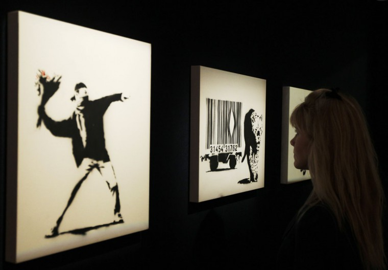 """A Bonhams employee poses for a photograph with Banksy's """"Love is in the Air"""" (left) and """"Leopard and Barcode"""" at Bonhams auction house in London on March 23, 2012. (REUTERS/Luke MacGregor )"""