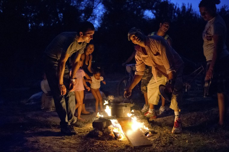 "Families from Romania stand near a fire as they prepare the dinner in front of makeshift shelters in a camp near the Garonne river in Toulouse, September 11, 2012. Around 130 Roma, referred to as ""Gens du Voyage"", live in this illegal camp, a low-lying area liable to flooding, without electricity and running water. Picture taken September 11, 2012. (Bruno Martin/Reuters)"
