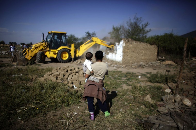 A Bulgarian Roma woman holds a child as they watch an excavator demolish a house in a Roma suburb in the town of Maglizh, some 260km (161miles) east of Sofia September 25, 2012. Municipal authorities started demolishing some 30 illegally built shacks and houses in the suburb on Tuesday. (Stoyan Nenov/Reuters)