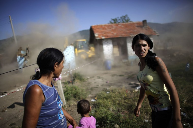 Bulgarian Roma women react as an excavator demolishes their house in a Roma suburb in the town of Maglizh, some 260km (161miles) east of Sofia September 25, 2012. Municipal authorities started demolishing some 30 illegally built shacks and houses in the suburb on Tuesday. (Stoyan Nenov/Reuters)