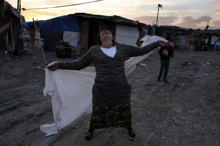 "A woman dances with a white sheet during a dance parade organized by community advocates on the streets of the Romanian gypsy settlement of ""El Gallinero"", in the outskirts of Madrid November 24, 2012. More than 400 Romanian gypsies live in precarious conditions, without running water or sewage services, in ""El Gallinero"", just 15 km (9 miles) away from Madrid's centre. The inhabitants live in ramshackle huts made out of cardboard and zinc in an area prone to flooding. They have no running water or sewer services. Their children play amidst garbage, copper cables and rats. Picture taken November 24, 2012. (Susana Vera/Reuters)"