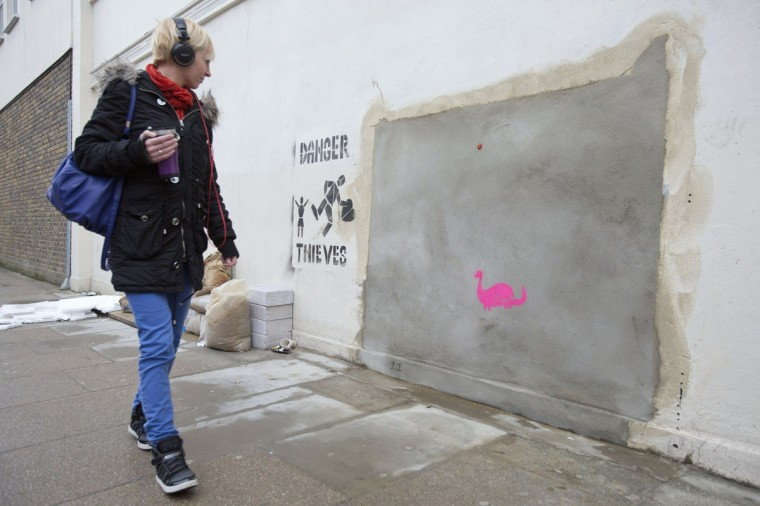 """A woman walks past the former site of """"Banksy: Slave Labour"""", a mural by graffiti artist Banksy, in north London on February 20, 2013. (REUTERS/Neil Hall)"""