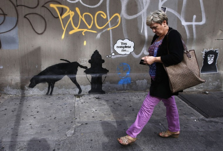 A woman walks past new artwork by British graffiti artist Banksy on West 24th street in New York City on October 3, 2013. (REUTERS/Mike Segar )