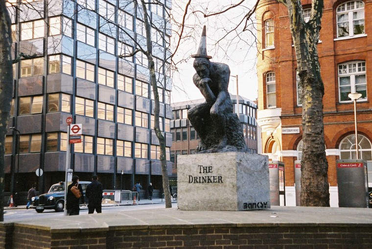 A statue deposited overnight without authorization at the junction of Shaftesbury avenue and St. Giles high street in London on February 27, 2004. The sculpture 'The Drinker,' which has a traffic cone permanently attached to its head, is a parody of Rodin's famous 'The Thinker', and a comment on binge-drinking and behaving badly in public by graffiti artist Banksy. (REUTERS/HO/Steve Lazarides)