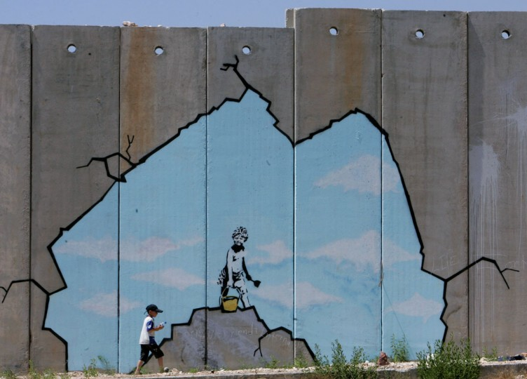 A Palestinian boy walks past a drawing by British graffiti artist Banksy near the Kalandia checkpoint in the West Bank. (REUTERS/Ammar Awad)