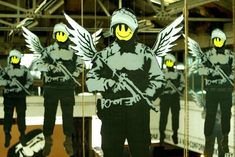 Cartoon images of policemen with wings and smiley faces hang in the Turf War exhibition by grafitti artist 'Banksy' in London's East End. (REUTERS/Peter Macdiarmid)