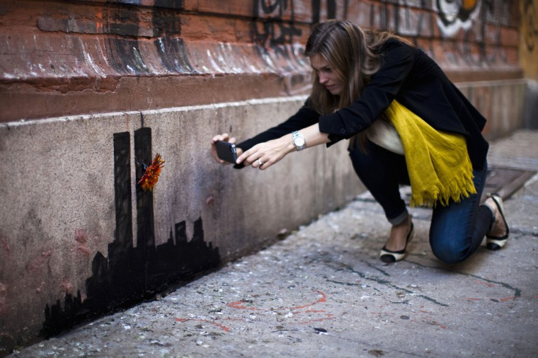 A woman takes a picture of an artwork by British graffiti artist Banksy at Lower Manhattan in New York City, on October 15, 2013. (REUTERS/Eduardo Munoz)