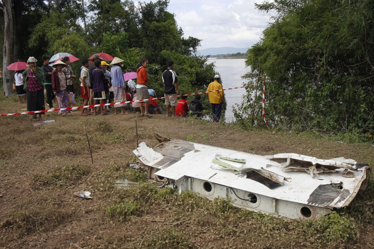 Villagers gather on the banks of Mekong river as rescue personnel on boats search the crash site of an ATR-72 turboprop plane, in Laos. (REUTERS/Chaiwat Subprasom)