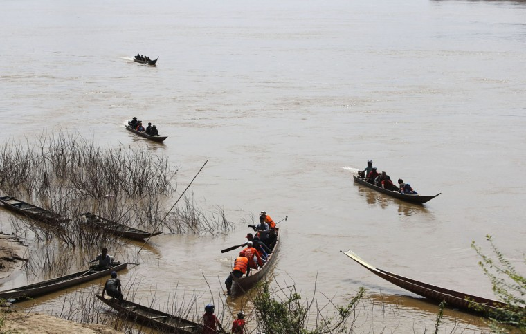 Rescue personnel on boats search the crash site of an ATR-72 turboprop plane in Laos. (REUTERS/Chaiwat Subprasom)