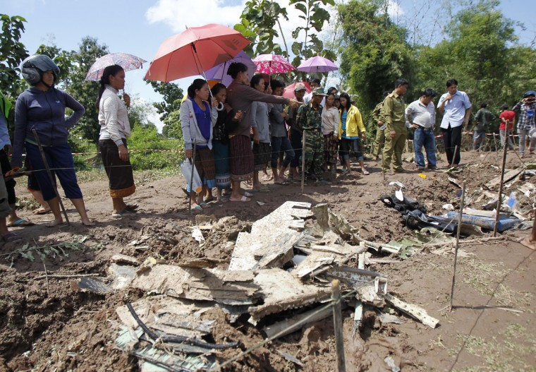 Villagers look at debris and luggage retrieved from the crash site of an ATR-72 turboprop plane in Laos. (REUTERS/Chaiwat Subprasom)