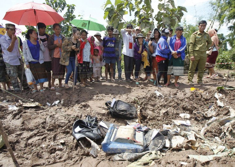 Villagers look at debris and luggage retrieved from the crash site of an ATR-72 turboprop plane in Laos. (REUTERS/Chaiwat Subprasom )